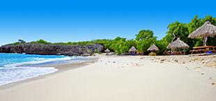 Wit strand met stukje zee en parasols op Curacao