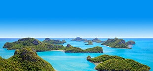 Zee met groene eilanden in Thailand
