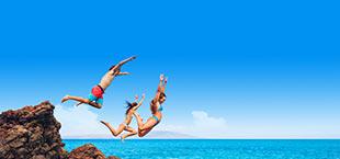3 jongeren die van een rots de zee in springen in Albufeira