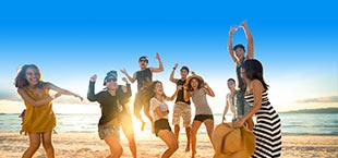 Jongeren op het strand aan de Costa Brava bij zonsondergang