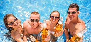 4 jongeren in het zwembad met een biertje