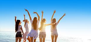 5 meiden enthousiast met de zee op de achtergrond