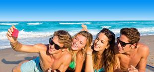 4 jongeren maken een selfie op het strand