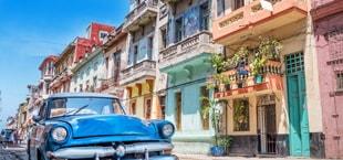 Blauwe oldtimer in een straat met gekleurde huizen in Havana, Cuba