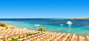 Strand in een privébaai van een resort in Egypte, vol met rieten parasols