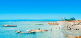 Strand en zee met bootjes in Gambia