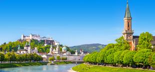 Meer met bewoonde berg en kerkje omringd door groene bomen in Oostenrijk
