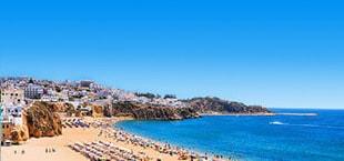 Wit strand met ligbedjes en helderblauwe zee