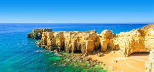 Gele rotsen bij blauw zeewater in Albufeira Portugal