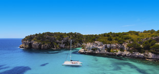 Baai met bootje en helderblauwe zee bij Menorca