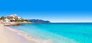 Uitzicht op het strand met hotels en bergen op de achtergrond op Mallorca