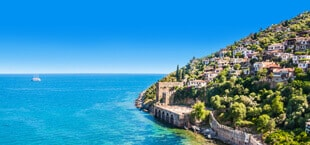 Blauwe zee met groene kust en huisjes in Turkije