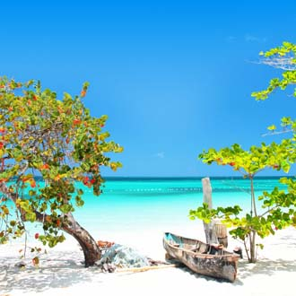 Foto van een blauwe zee met wit zandstrand, groene bomen en een bootje