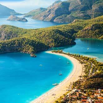 Baai met helderblauwe zee en beboste bergen aan de Lycische Kust