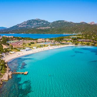 Blauwe baai met een strand en bomen Olbia