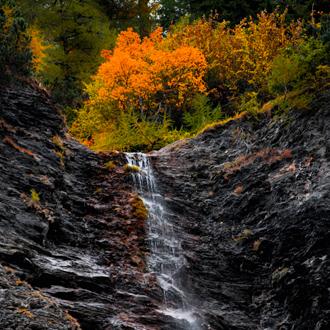 Kleine waterval in de bergen met gekleurde bomen in Crans Montana