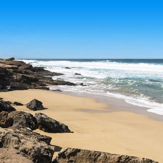 Kustlijn met aan een klein strandje met rotsen op Fuertaventura.