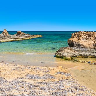 Het wilde strand met helder turquoise water in Malia op Kreta
