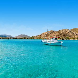 Een vissersbootje op helderblauw zeewater op Paros