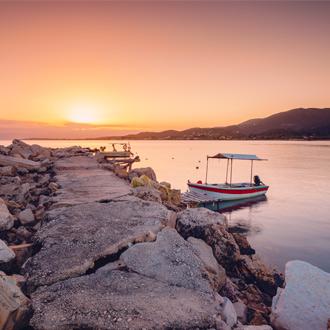 Zonsondergang en een vissersbootje op het Griekse eiland Corfu