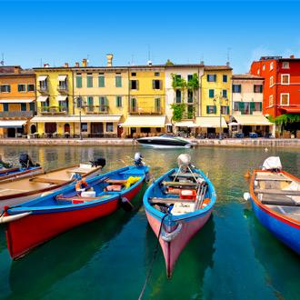 De haven van Peschiera del Garda met gekleurde bootjes en huisjes, Italië