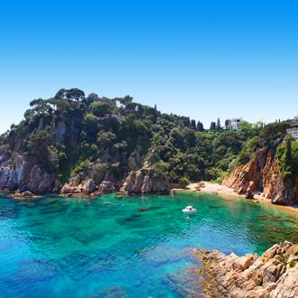 Helderblauwe zee omringd door rotsen aan de kust van Blanes in Spanje