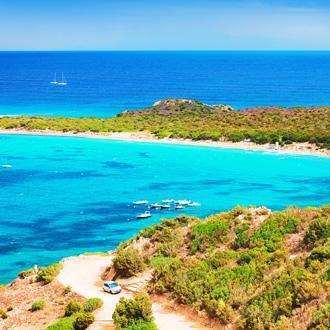 Groen landschap met weg omringd door zee in Sardinie