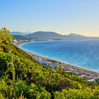 Groene bergen, uitkijkend over de kustlijn met azuurblauwe zee in Ixia