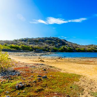 zoutpannen Jan Thiel, met groene bergen en blauwe helder blauw water