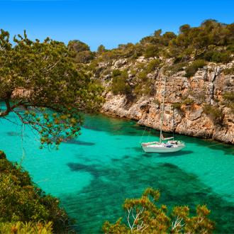 Een kleine jacht op azuurblauwe zee in het dorp Cala Pi op Mallorca
