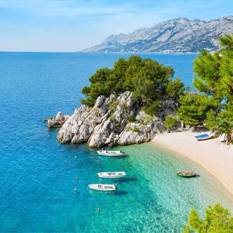 Het strand en helderblauw zeewater met bootjes in Brela, Kroatie