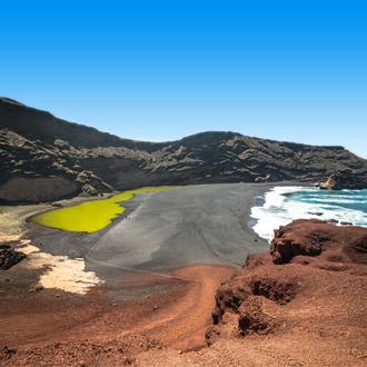 Een groen lagune aan de kustlijn in Lanzarote.