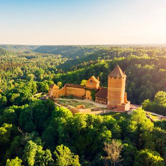 Een kasteel omgeven door bossen in Letland