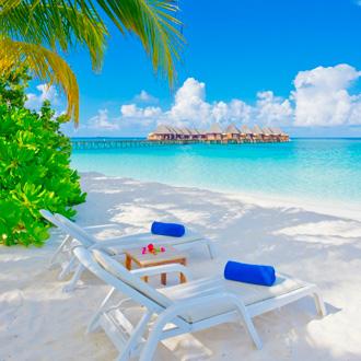 Foto van strand en zee met ligbedjes en resort