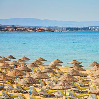 Parasols en ligbedjes op het strand van Cesme