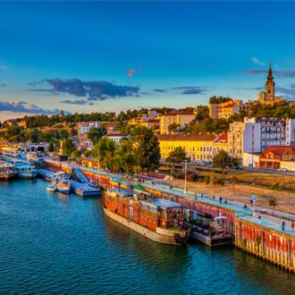 Zonsondergang over Belgrado met schepen in de haven