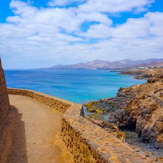 Bergpad met uitzicht over de azuurblauwe zee, tussen Puerto del Carmen en Puerto Calero