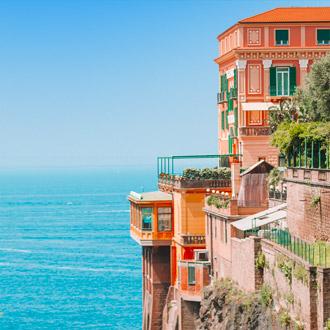 Kleurrijk oranje gebouw op een steile klif en zee in Sorrento