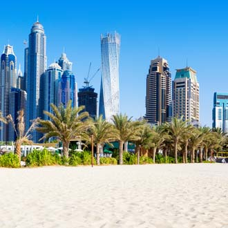 Strand van Dubai met hoge wolkenkrabbers en blauwe lucht