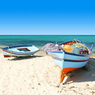 Strand met zee en bootjes Tunesie