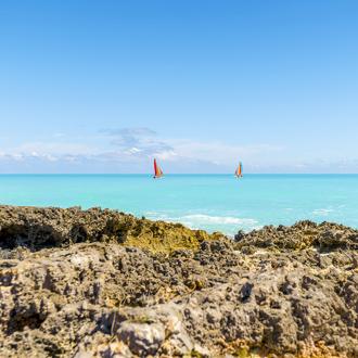 Rots met blauwe zee en zeilboten bij Cayo Santa Maria