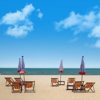 Het strand van Cha Am met strandstoelen, parasols en uitzicht op de zee in Midden Thailand