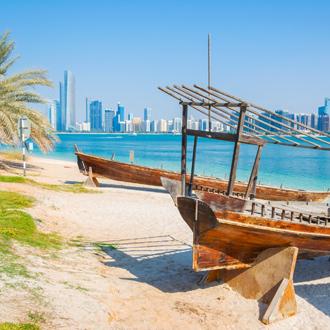 Strand met houten bootjes in de zee en wolkenkrabbers op de achtergrond in Abu Dhabi