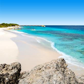 Wit zandstrand met helderblauw zeewater op het eiland Bonaire