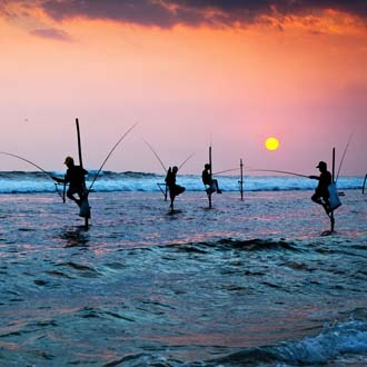 Vissers in traditionele houding bij Galle Sri Lanka
