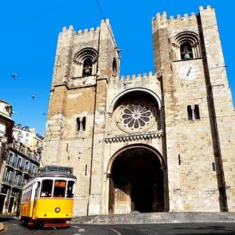 Gele tram voor een kerk in Lissabon