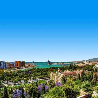 Uitzicht over groene bomen en de zee in Malaga