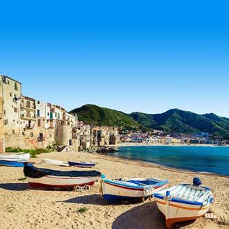 Oude vissersbootjes op het strand bij Cefalù met bergen op de achtergrond