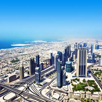 Blik van boven op wolkenkrabbers, wegen en zee Dubai