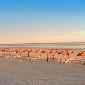 Zonsondergang op het strand met parasols en ligbedden in Monte Gordo, Portugal